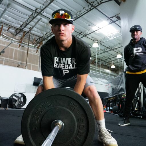 man lifting weight while coach watches